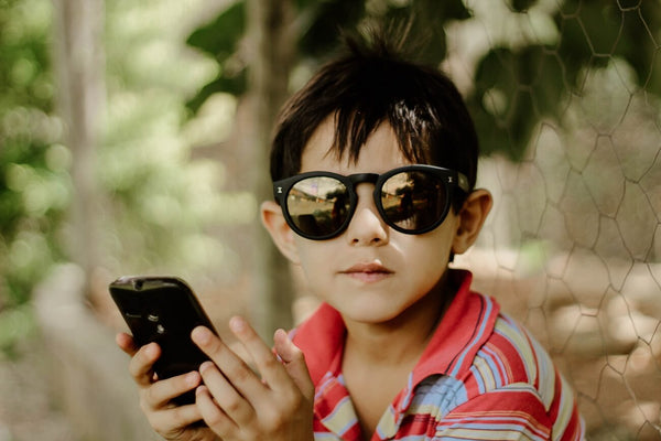 Kid with sunglasses on looking at a smartphone