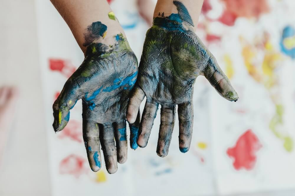 Kids hands covered in blue paint from painting
