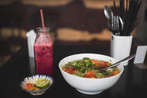 A bowl of soup on a black surface with a jar full of a smoothie-like drink