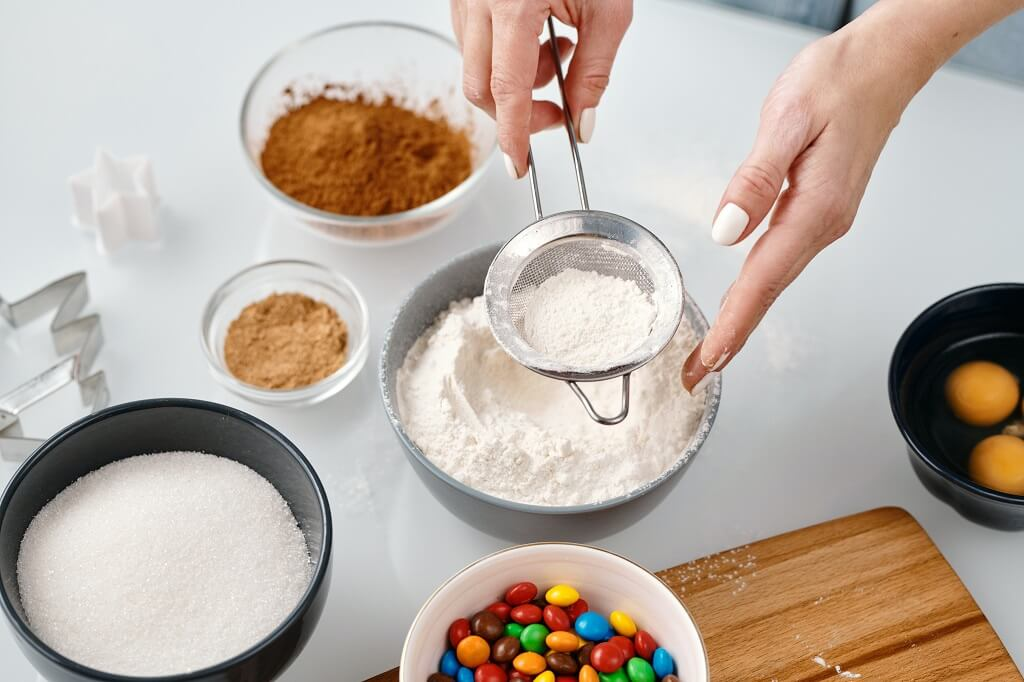 Woman baking with sugar, flour, eggs, and candy