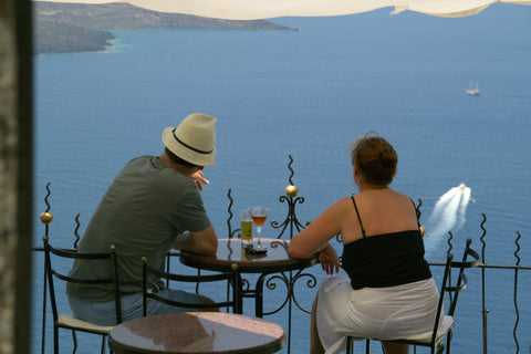 Two people sit at a table with no food, overlooking a large body of water