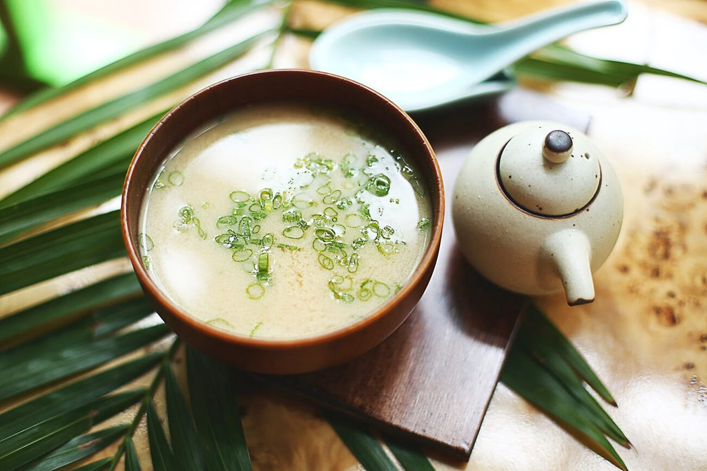 Photo of miso soup in a bowl next to a teacup