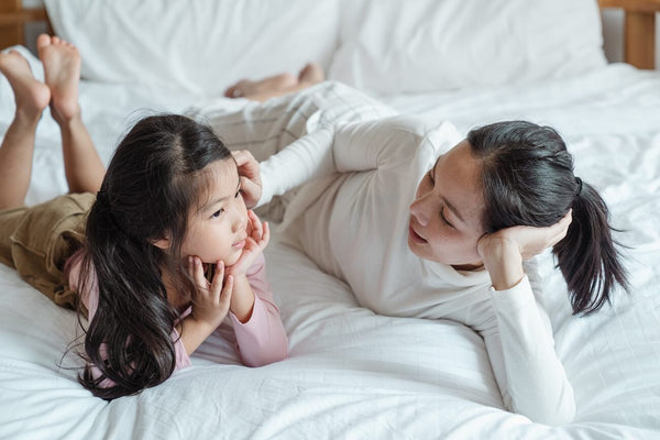 Mom laying on white bed with her daughter having a conversation