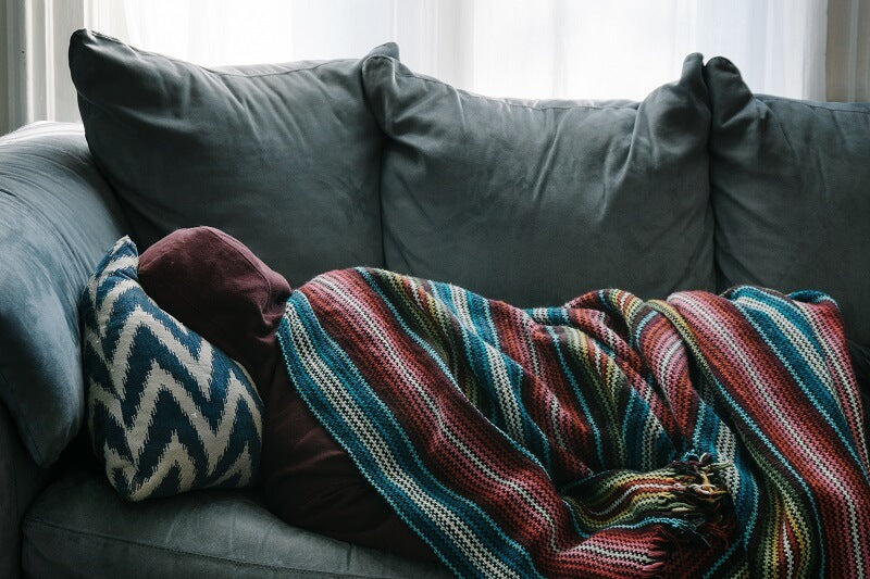 Person laying on the couch covered in blankets