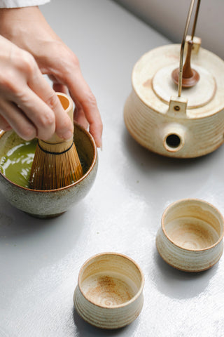 A single hand using a mortar and pestle to grind up matcha near a tea kettle and two cups