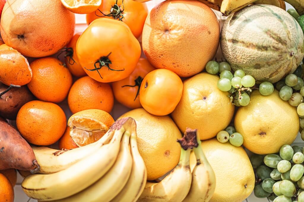 Prebiotic-rich fruits including bananas, oranges, grapes, and melons