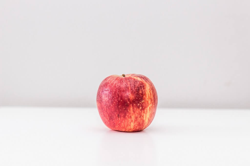 Red apple on a white countertop