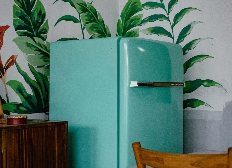Turquoise refrigerator in the corner with floral wallpaper behind it