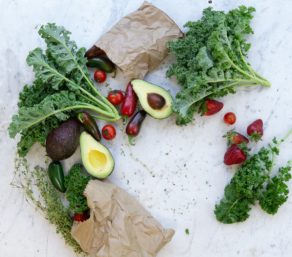 Kale, avocadoes, and other veggies laid out on the kitchen counter
