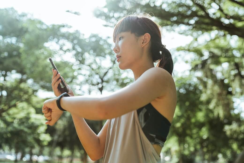 Woman checking her fitness tracker at the park while on a run