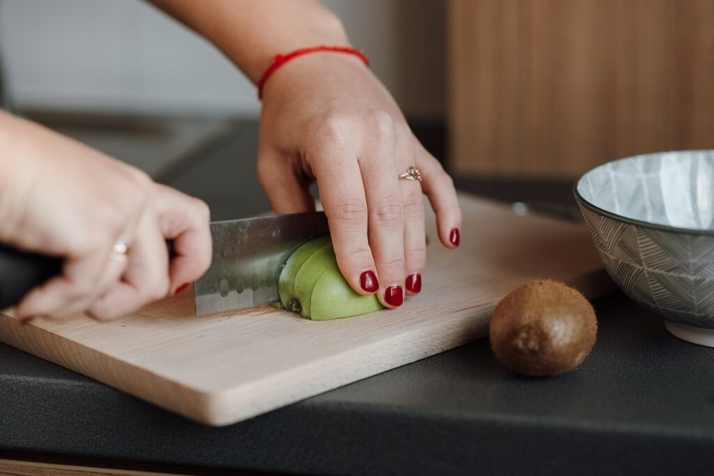 Woman cutting a green apple for fiber