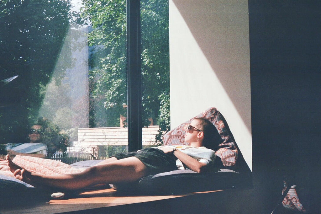 Woman laying by the window looking at the trees to destress from burnout