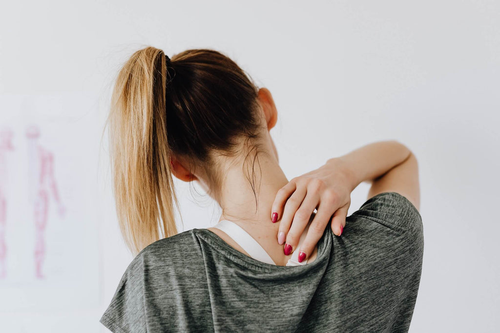 Woman massaging back to ease pain