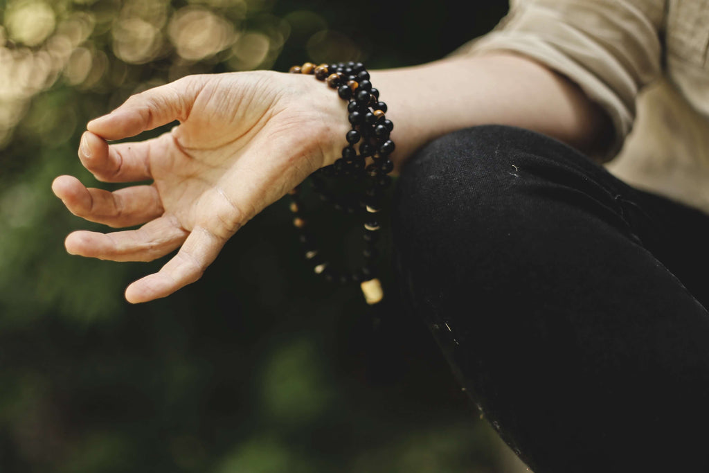 Hand on knee of person meditating outdoors