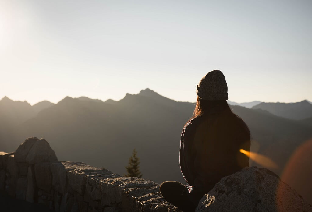 Woman meditating outside overlooking mountains