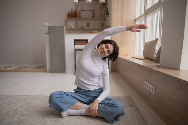 Woman smiling in yoga pose in her home