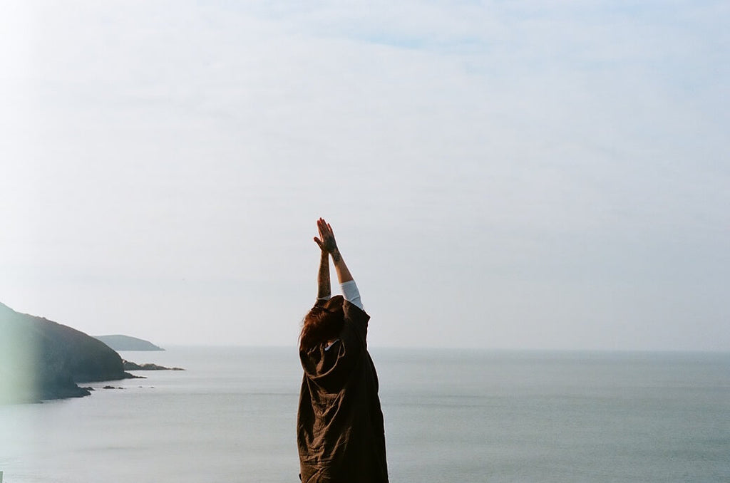 Woman with arms outstretched near the ocean for stress relief