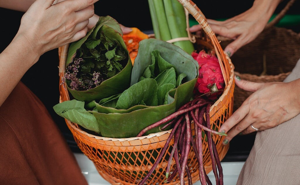 Women holding green leafy vegetables in a basket
