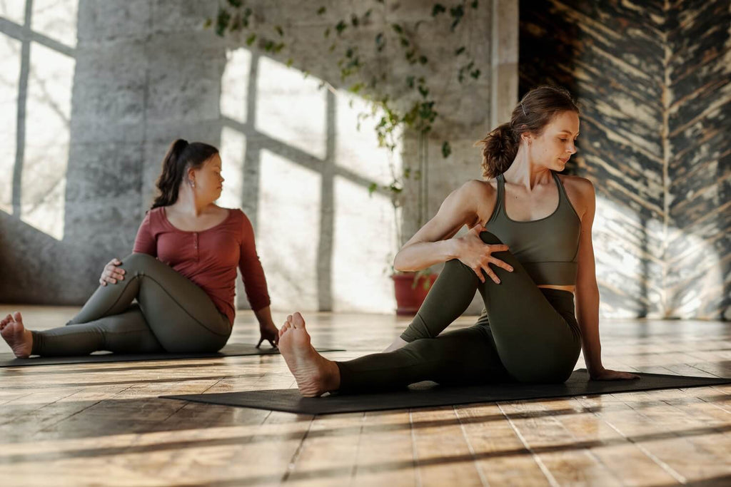 Two women stretching their backs on yoga mats