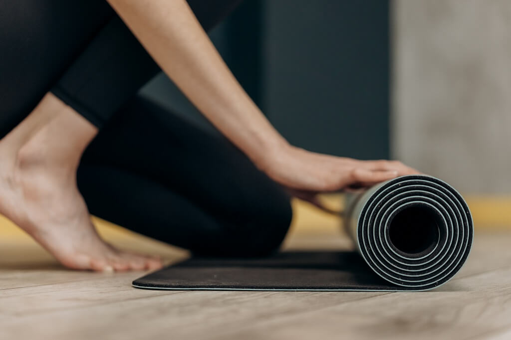Woman rolling up a yoga mat after exercise