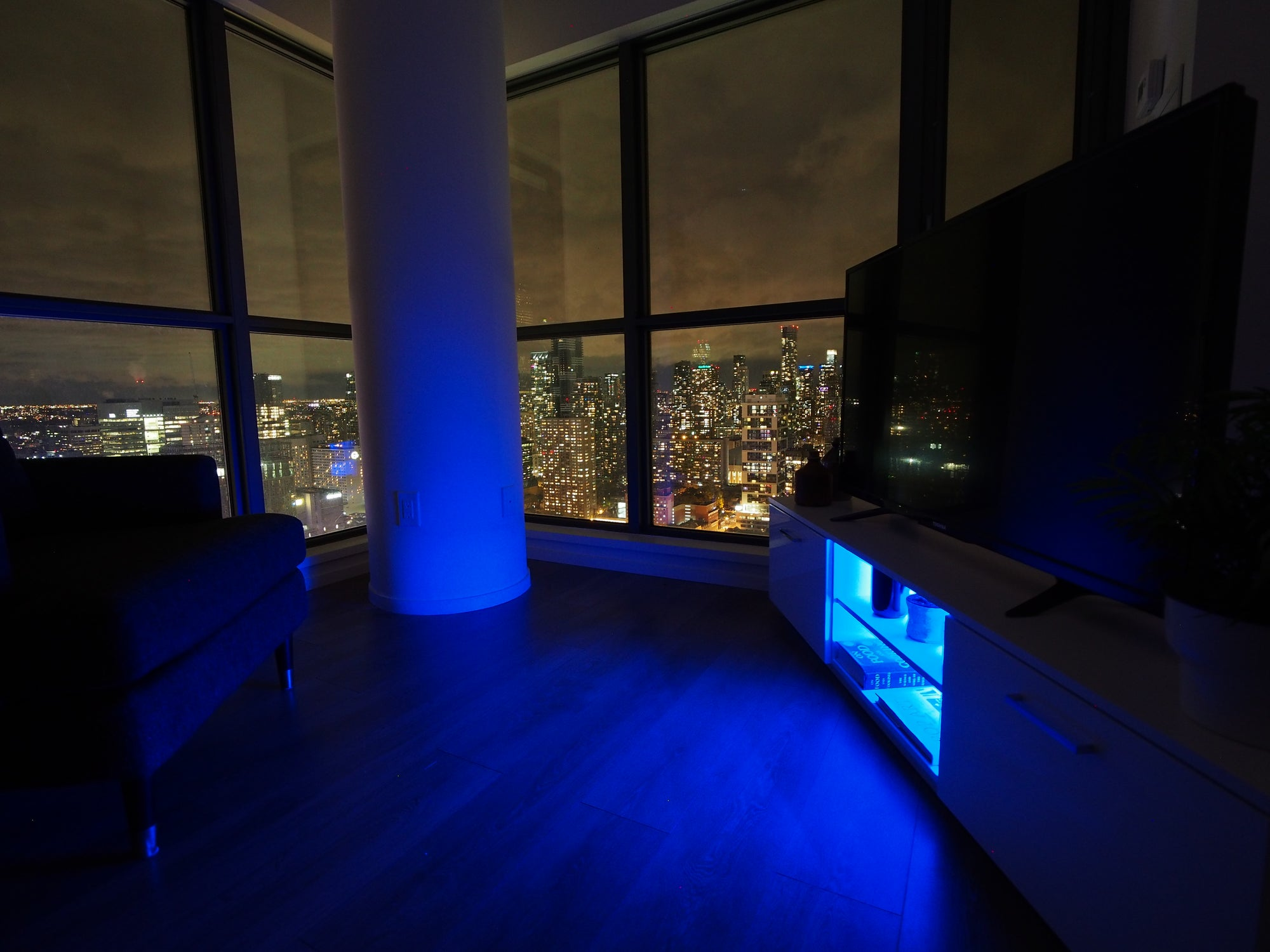Blue LED lighting on the White Roskilde TV Cabinet in modern condo and skyline
