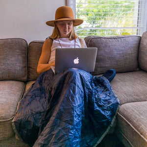 Woman using Blue Layover Travel Blanket while working on laptop
