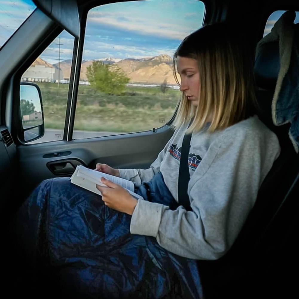 woman using layover blanket in car reading a book