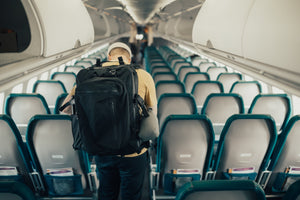 Man walking down airplane with 42 Liter backpack and 11 Liter Backpack.