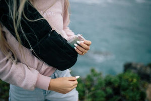 Woman holding wallet going inside of 2 Liter Sling Bag