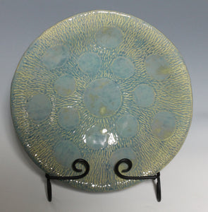 Medium two-tone ceramic bowl features carved radiating lines with large burnished planetary circles.