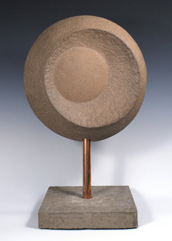 Large circular ceramic sculpture with convex and concave surfaces mounted on custom base with copper piping through a concrete base