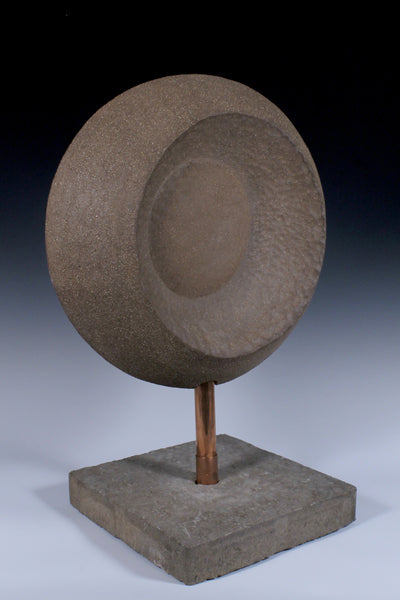Back view of Large circular ceramic sculpture with convex and concave surfaces mounted on custom base with copper piping through a concrete base
