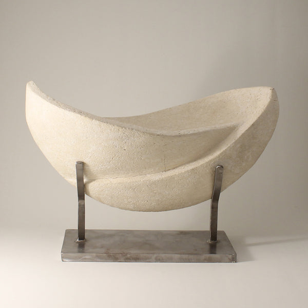 White sculpture with two interconnected curvaceous wings resting on a custom metal stand