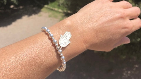 The RAW Good Karma Bracelet features a Hamsa hand hand charm and is made from recycled Sterling silver beads