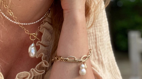 Image of the gold vermeil and freshwater pearl designs by RAW Copenhagen here modelled on wrist and neck on a summers day in Kent