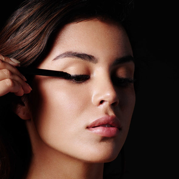 Hold the skin taut to help create a smooth canvas. Starting at the outer corner of the eye, using Defining Liner trace just above the lash line to the inner corner of the eye. Use the smudging tool at the opposite end of the pencil to soften and blend.