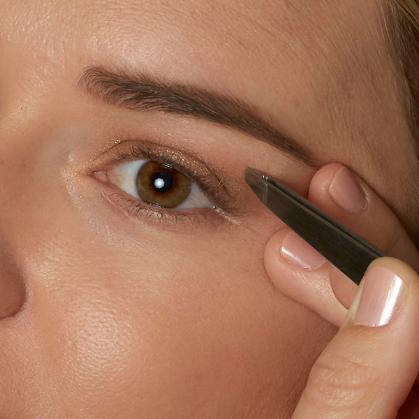 Tweeze stray hairs around the brow arch, removing only the obvious course/dark hair especially between the eyes.