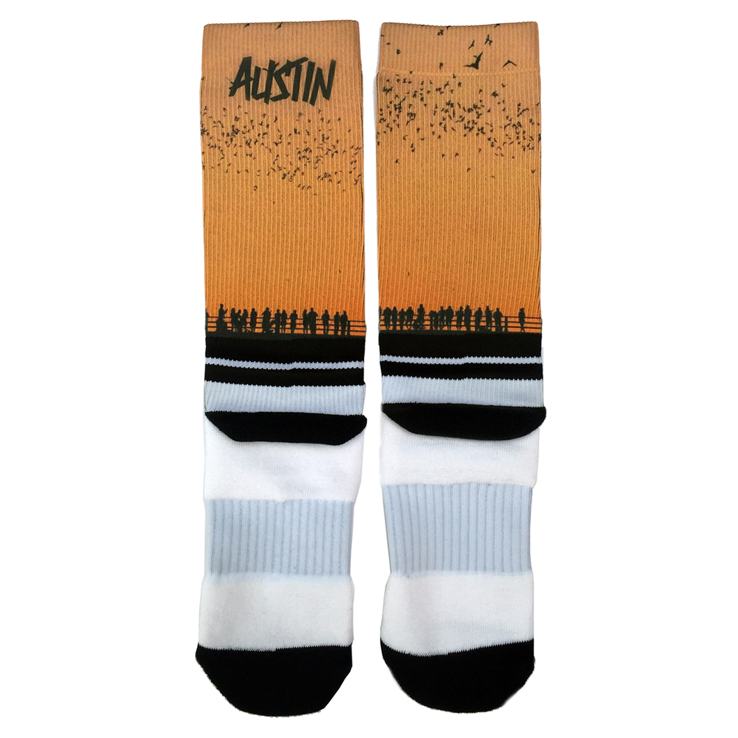 Austin socks with orange sunset and a silhouette people watching the bats fly