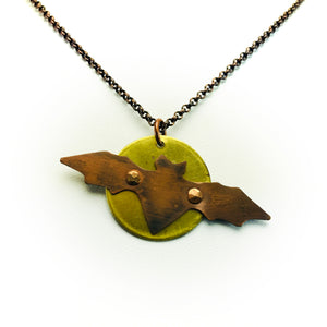 Necklace with hand cut copper bat attached with rivets to full moon made of brass