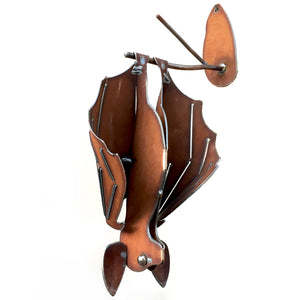 Hanging bat sculpture of cinnamon-rusted metal with eyes like liquid mercury