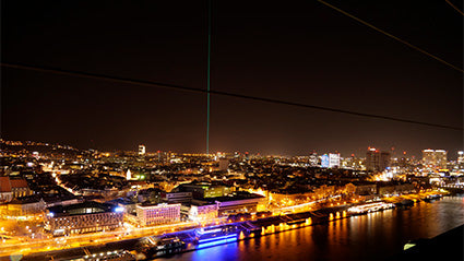 Green sky laser beam from in city