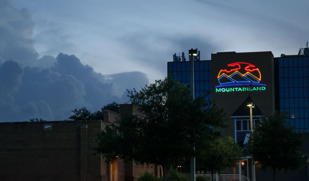 Mountainland logo projected on building with laser