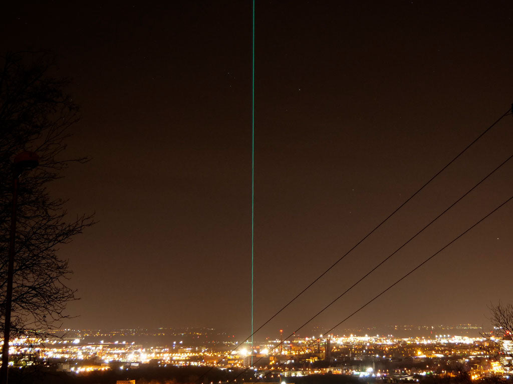 Outdoor photo of sky laser system projecting into the sky