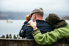 Photo of a man and woman with their backs to us, sitting on a bench looking out over the water.