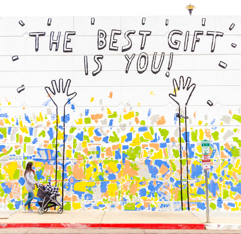 """Photo of woman with a stroller walking by a colorful graphic mural with text that reads: """"THE BEST GIFT IS YOU!"""""""