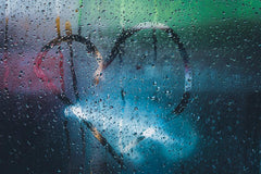 Condensation on window glass make raindrops glow.  Someone has traced a heart shape on the inside of the glass with their finger.