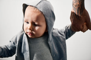 Baby boy kind wearing grey baby hooded cardigan with white draw strings made of organic cotton
