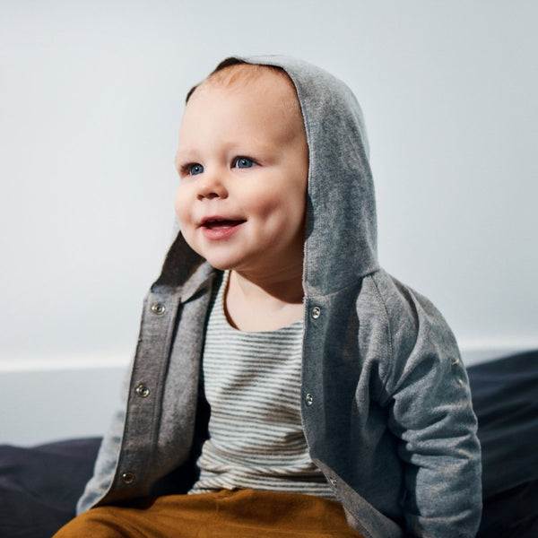 Laughing baby wearing grey baby hooded cardigan with white draw strings made of organic cotton kind