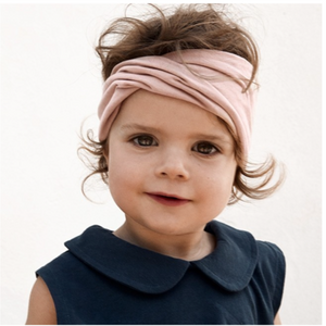 Girl wearing headband with a twisted front in vintage pink made of organic cotton.