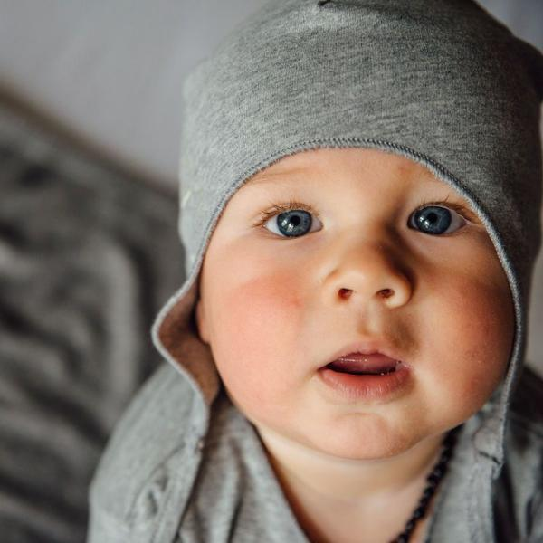 baby wearing grey melange baby hat with strings gray label by KiND
